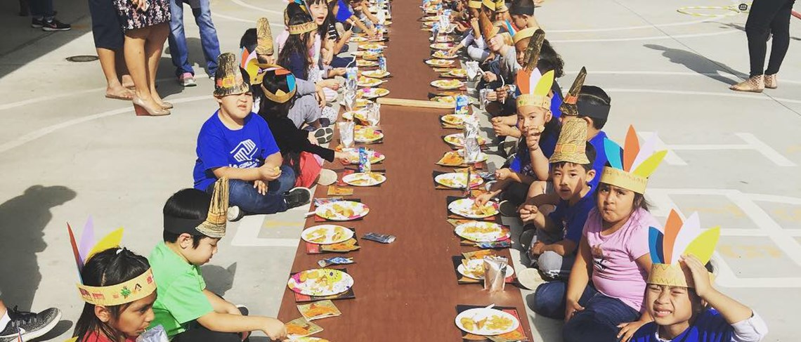 Kindergarten students eating a Thanksgiving meal as a class.